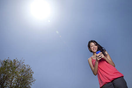 Low angle view of woman text messaging on a sunny day