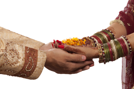 Close-up of bride and grooms hands with marigold Stock Photo