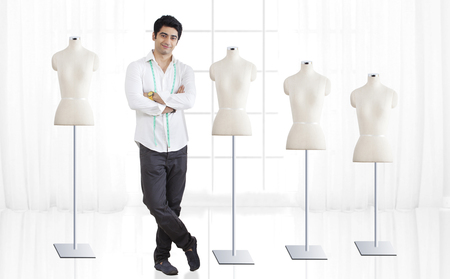 human likeness: Full length of young male fashion designer standing by mannequin at studio