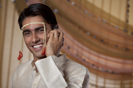 marathi: Handsome young man speaking on mobile phone Stock Photo