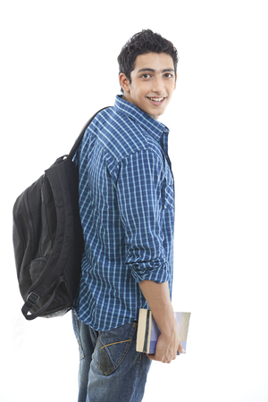Portrait of aspiring young man with book and bag over white background