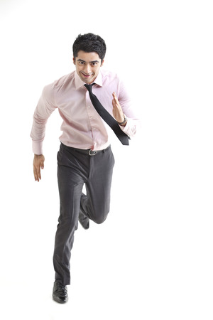 welldressed: Excited businessman running over white background