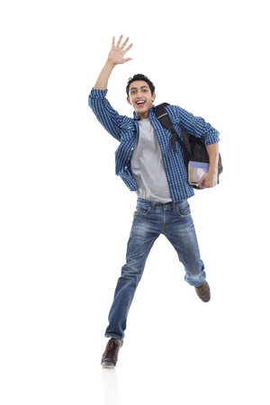 Excited young college student waving over white background