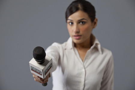 welldressed: Close-up of young woman news reporter holding out microphone Stock Photo