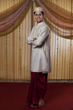 kurta: Full length of Indian groom smiling with arms crossed Stock Photo
