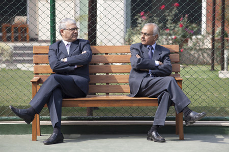 legs crossed at knee: Senior male business executives staring at each other while sitting arms crossed on bench in tennis court