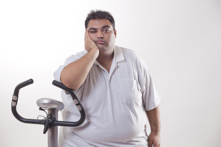 Portrait of a lazy obese man with an exercise bike over white background