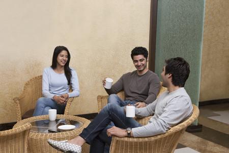 집에서 고리 버들의 자에 앉아있는 동안 함께 커피를 마시고 행복 젊은 친구