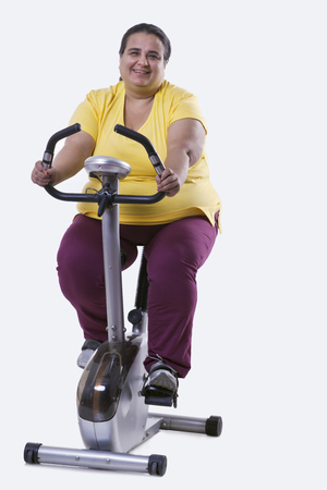 Portrait of an overweight woman exercising over white background Stock Photo