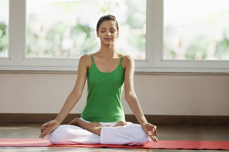 concern: Young man meditating in morning on exercise mat Stock Photo