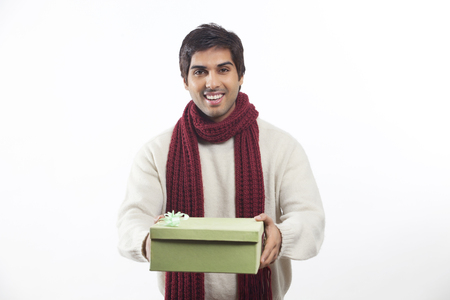 Smiling young man holding gift box over white background Banco de Imagens