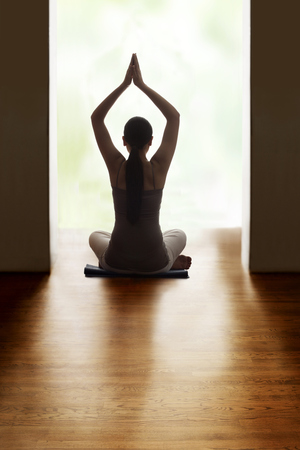 Rear view of young woman meditating on hardwood floor while raising hands Stock Photo