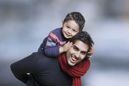 Father giving boy piggy back ride outdoors Stock Photo
