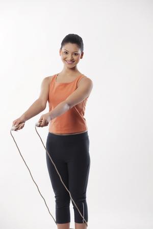 Foto de archivo - Retrato de una mujer joven con saltar la cuerda sobre  fondo blanco 3f779f6d025
