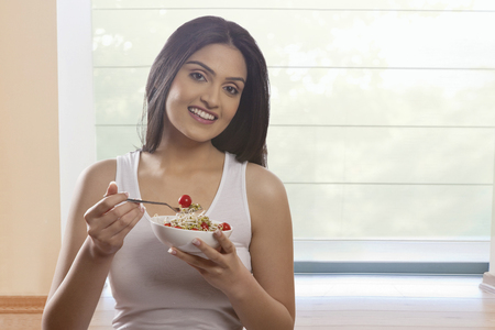 Portrait of happy young woman eating bean sprouts and cherry tomatoes