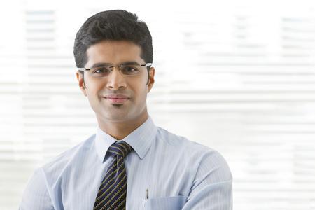 Portrait of young businessman smirking