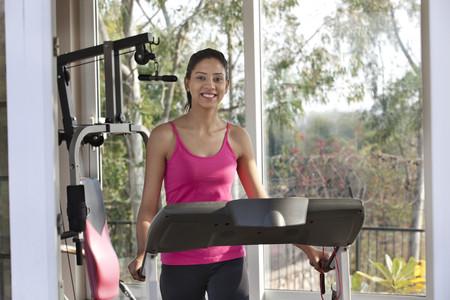 디딜 방아에 운동하는 동안 웃 고 행복 한 젊은 여자의 초상화