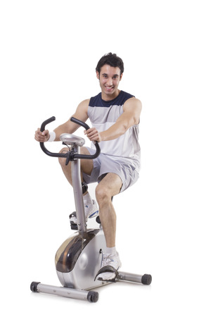 concern: Portrait of a young fit man on exercise bike over white background