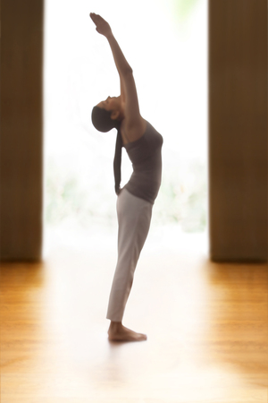 Profile shot of young woman doing back bend yoga pose on hardwood floor