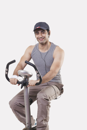 Portrait of a young man listening music while exercising over white background