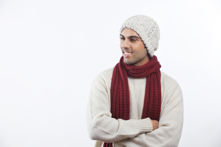Happy young man with arms crossed standing over white background Stock Photo