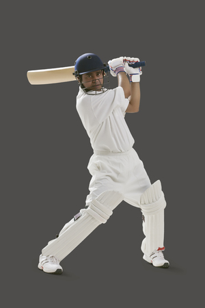 Portrait of young man playing cricket isolated over gray background