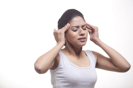 Young woman suffering from headache isolated over white background