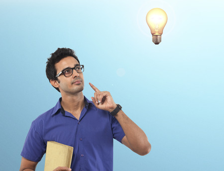 Young man with a book getting an idea Stock Photo