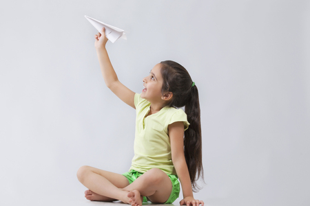 Happy girl playing with paper airplane isolated over gray background Stock Photo