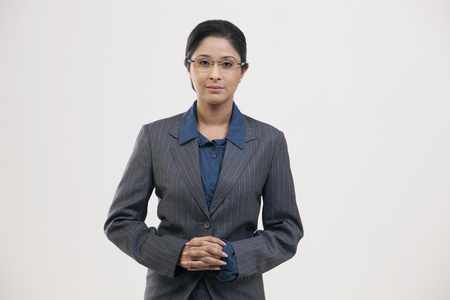 welldressed: Portrait of young businesswoman in suit isolated over gray background