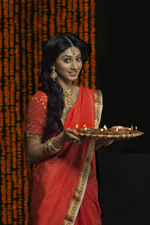 Portrait of woman holding a tray of diyas Stock Photo