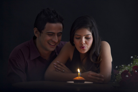 engage: Woman blowing out a candle in a muffin