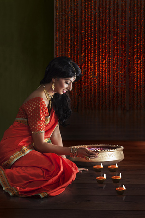 one item: Woman arranging diyas