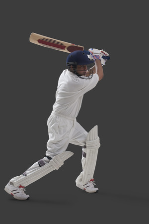 Young male player playing cricket isolated over gray background Stock Photo