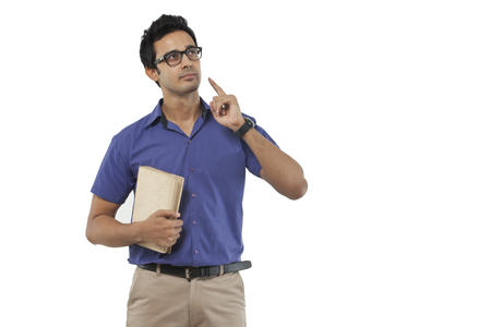 front view: Young man with a book thinking Stock Photo