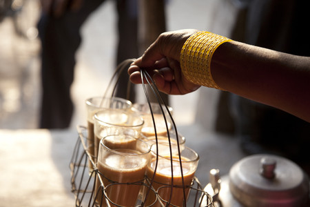 Close-up of females hand holding tray of fresh morning chai