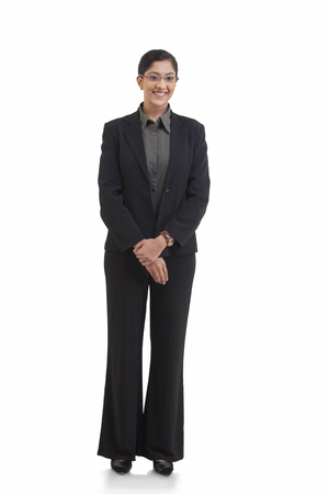 welldressed: Full length portrait of happy businesswoman standing against white background