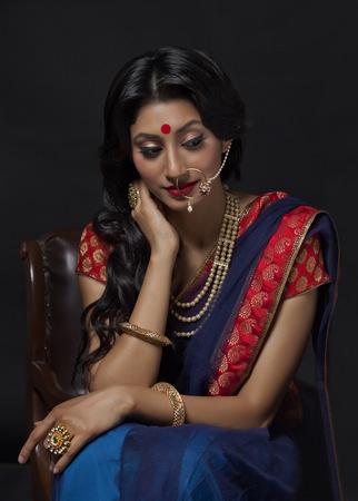 furniture: Beautiful bride with jewelery sitting