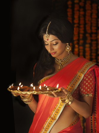 down lights: Woman holding a tray of diyas