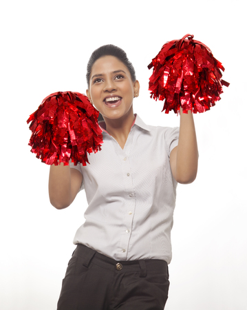 Happy cheer leader with pompoms screaming against white background Stock Photo