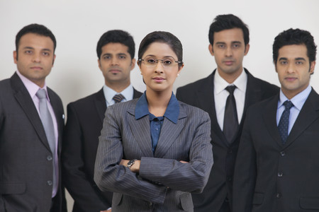 Group portrait of confident business people standing against gray background