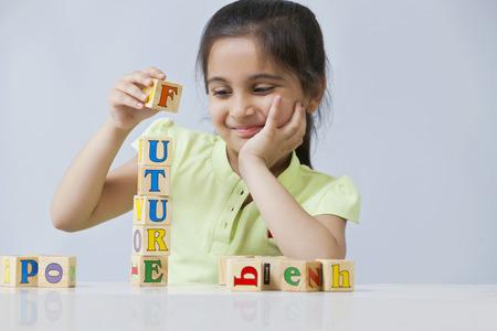 少女は青い背景に分離されたブロックを積み重ねる