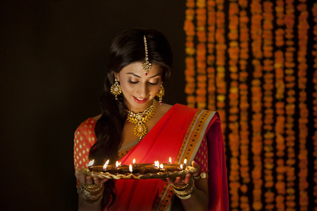 Woman holding a tray of diyas