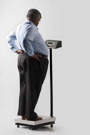 Obese man checking his weight Stock Photo