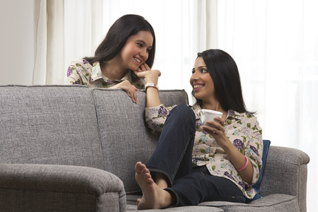matching: Mother looking at her daughter sitting on sofa drinking tea