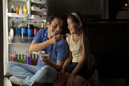 refrigerator: Father feeding cake to daughter in front of open refrigerator