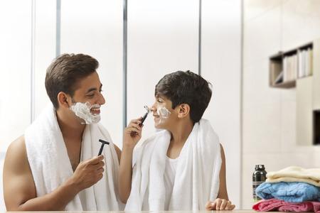 Boy lathering fathers nose Reklamní fotografie