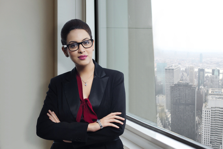 welldressed: Portrait of confident businesswoman standing by window in office Stock Photo