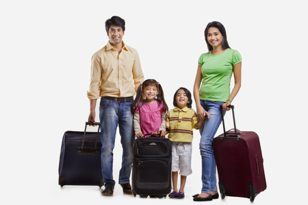 Portrait of family with suitcases