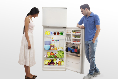 Young couple searching food in the fridge